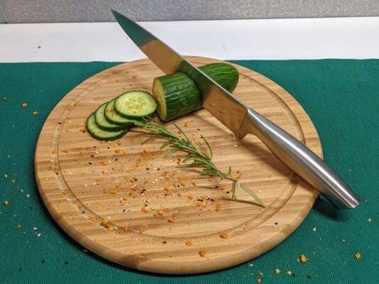 Schneidebrett aus Bambus, rund 30 cm Durchmesser, mit Gurke und Messer